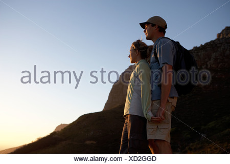 Couple with rucksack standing on mountain at sunset looking at view smiling profile - Stock Photo
