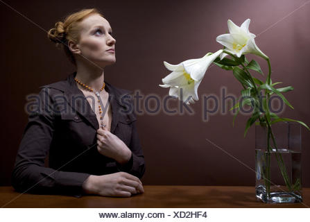 Woman, young, rehaired, necklace,  Wreath of roses, gaze upwards, prayer,  Portrait, vase, lilies,  Series, 20-30 years, high plug-in hairdo, chain, cross, prayer, consciousness, contemplation, trust, strength, inspiration, belief, religion, Spiritualität, Christian, silence, silence, bigoted, transfigures, Lifestyle, studio, indoors, sound in sound, brown sounds, color, color mood brown, flower vase, flowers, lily blooms, knows, - Stock Photo