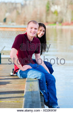 Beautiful young interracial couple sitting on wooden dock over lake, dangling feet over sides - Stock Photo