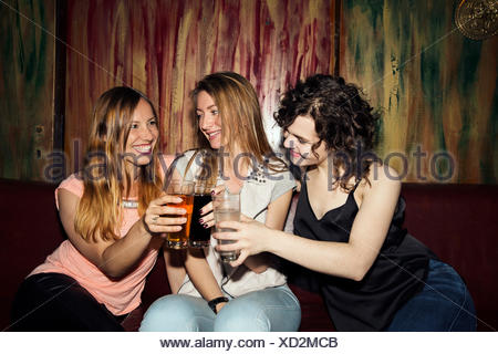 Three adult female friends raising a glass whilst sitting in bar - Stock Photo