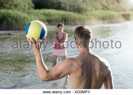 Mature couple playing volleyball at the lake, Bavaria, Germany - Stock Photo