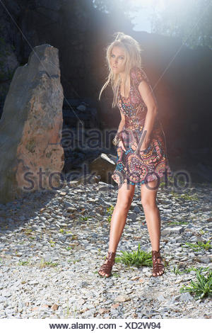 Young woman standing in quarry, looking away - Stock Photo