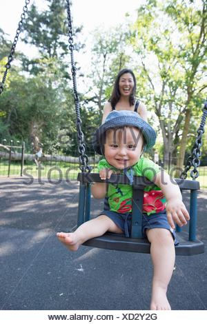 Portrait of baby boy with mother playing on park swing - Stock Photo