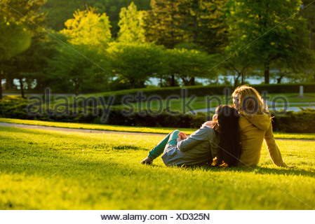 Two young women relaxing in park - Stock Photo