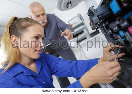 Female technician working on photocopier - Stock Photo