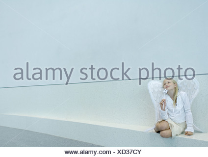 Girl wearing angel wings and holding wand - Stock Photo