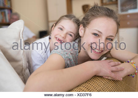 Portrait of sisters sitting on couch in living room, smiling - Stock Photo