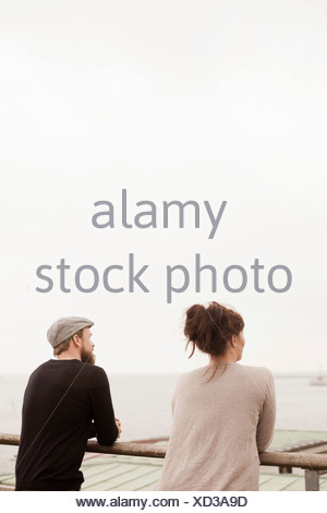 Rear view of business people standing by railing against clear sky - Stock Photo