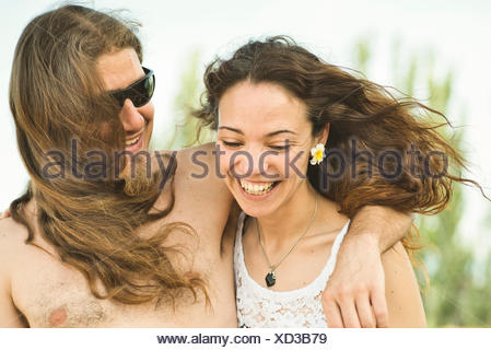 Portrait of happy couple on windy summer day - Stock Photo