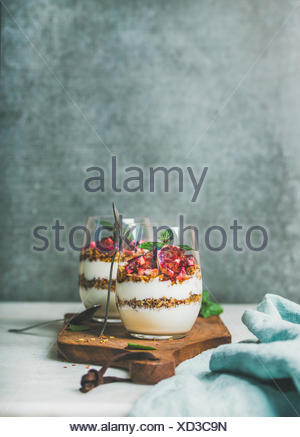 Healthy breakfast. Greek yogurt, granola, blood orange layered parfait in glasses with mint on wooden board, grey concrete wall at background, copy sp - Stock Photo