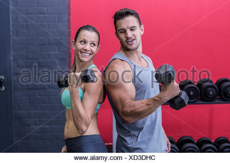 Muscular couple giving back to back - Stock Photo