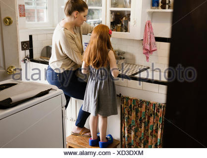 Girl and mother baking together in kitchen - Stock Photo