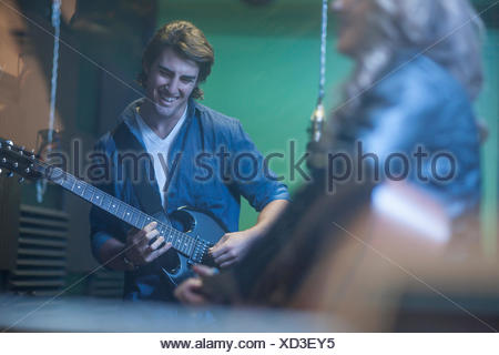 Two musicians in recording studio, playing guitar - Stock Photo
