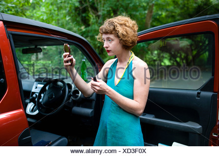 Woman in forest looking at compact mirror - Stock Photo