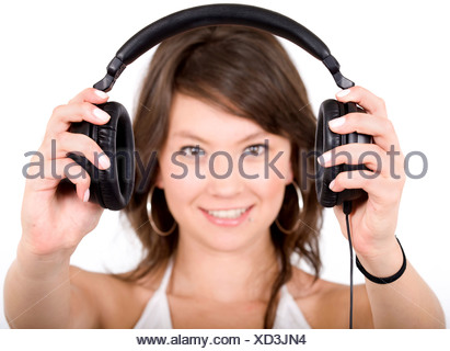 girl holding headphones in front of the camera - Stock Photo