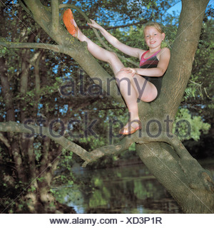 Girl perched in a tree over a river - Stock Photo