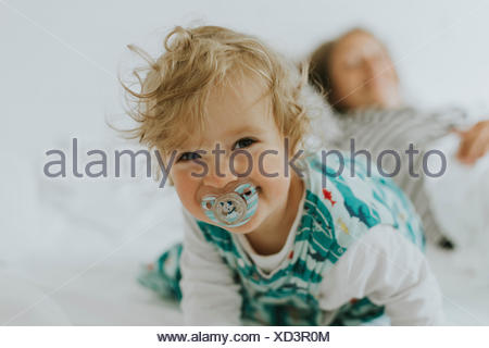 Portrait of happy little girl with mother in bed - Stock Photo