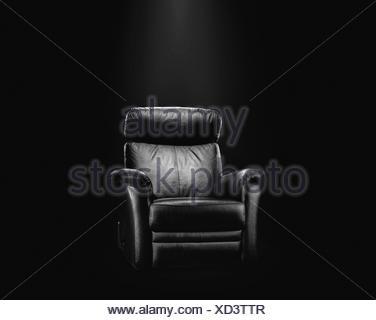 Black leather armchair in spotlight, dark background. - Stock Photo