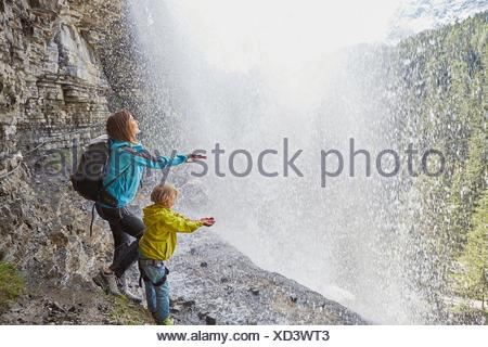 Mother and son, standing underneath waterfall, hands out to feel the water, rear view - Stock Photo
