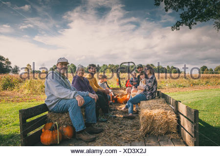 Extended family sitting in a hay wagon at a pumpkin patch - Stock Photo