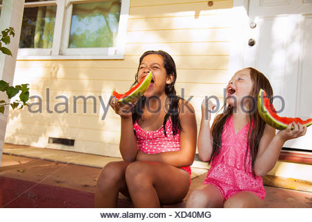 Two laughing girls sitting on house porch with slices of watermelon - Stock Photo