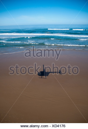 helicopter shadow flying over a beautiful beach - Stock Photo