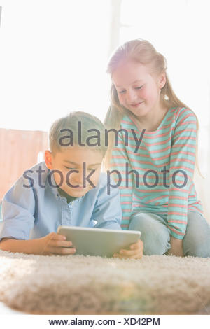 Siblings using digital tablet on floor at home - Stock Photo