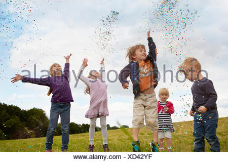 Five little children throwing confetti on a meadow - Stock Photo