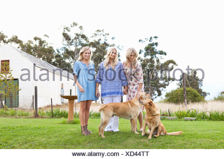 Mother and daughters with dogs in garden - Stock Photo
