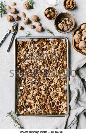 A few cups of mixed nuts are placed on a rimmed baking sheet to be toasted in the oven. - Stock Photo