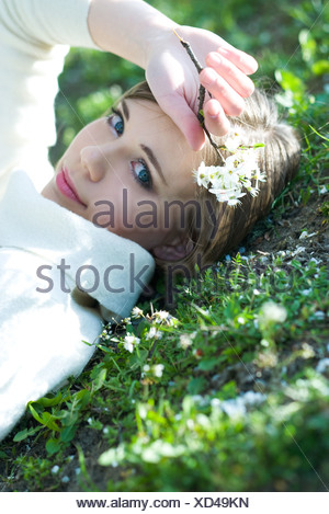 Teenage girl lying on the ground, holding flowers, smiling at camera - Stock Photo