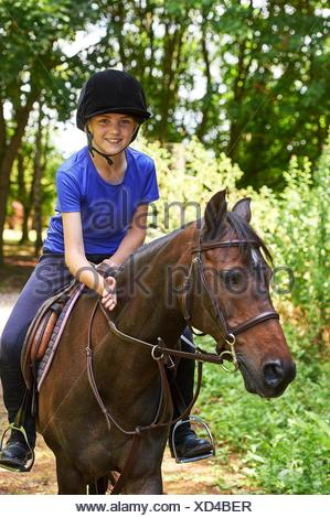 Girl on horse wearing riding hat looking at camera smiling - Stock Photo