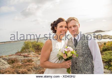 Sweden, Swedish West Coast, Bohuslan, Newly wed couple on sea coast - Stock Photo