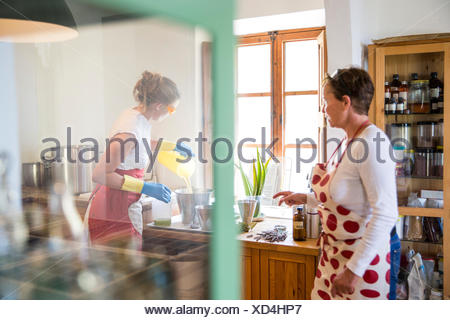Young woman pouring liquid lavender soap into bowl in handmade soap workshop - Stock Photo