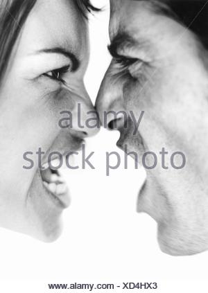 Couple arguing face to face pushing noses against each other shouting both aggressive expressions - Stock Photo