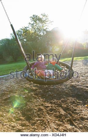 Sweden, Sodermanland, Arsta, Little boy (4-5) and girl (2-3) in round swing at sunlight - Stock Photo
