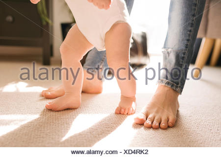 Mother and baby's bare feet on carpet in living room - Stock Photo