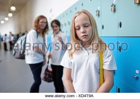 Schoolgirl being bullied in school corridor - Stock Photo