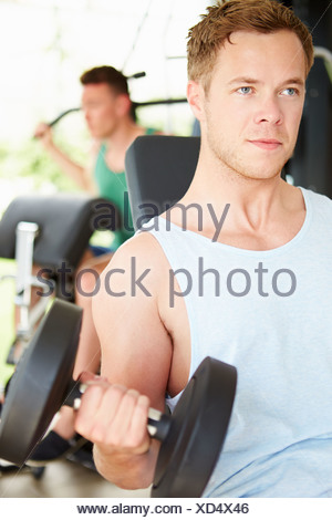 Two Young Men Training In Gym With Weights - Stock Photo