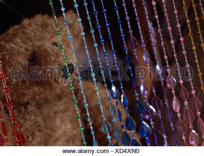 Close-up of a beaded curtain and a teddy bear - Stock Photo