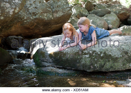 Girls lying on rock by river - Stock Photo