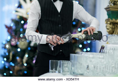 Waiter pouring glasses of champagne - Stock Photo