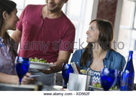 A cafe interior. A man in a waiter's apron serving a meal to two women at a table. - Stock Photo