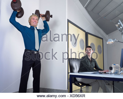 Office worker lifting weights - Stock Photo