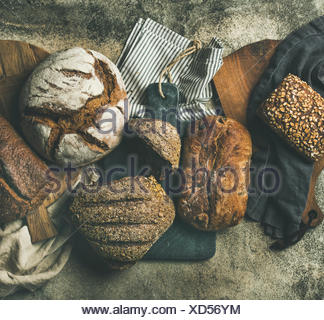 Flat-lay of various bread selection. Rye, wheat and multigrain rustic bread loaves on kitchen towels and boards over grey concrete stone background, t - Stock Photo