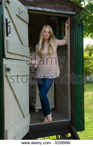 Teenage girl standing in doorway - Stock Photo