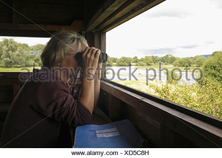 woman person birdwatching bird watch watching binocular hobby hobbies pastime hide reserve powys wales welsh britain british - Stock Photo