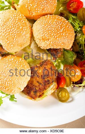 four fresh and delicious mini chicken burgers on a plate ,close up. - Stock Photo