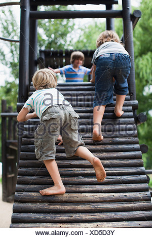 Boys playing on play structure together - Stock Photo