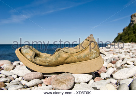 Old damaged shoe on stone beach - Stock Photo